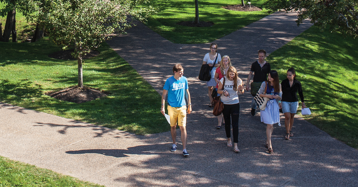 A group of students walking in the quad on a warm summer afternoon.