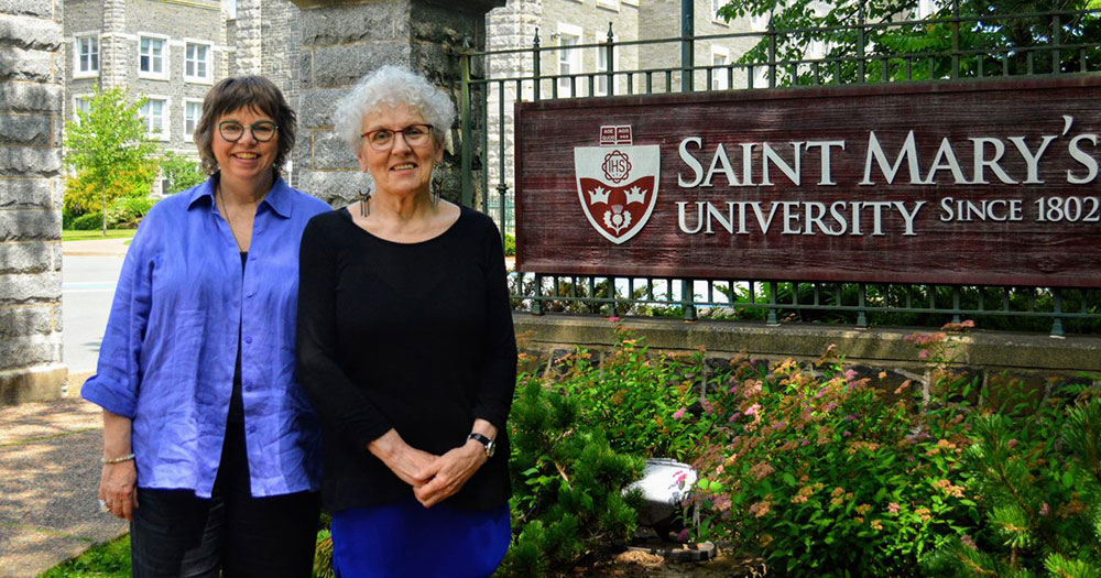 Linda MacDonald and Jeanne Sarson beside the Saint Mary's University sign.